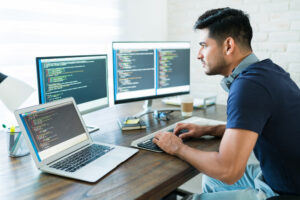Handsome Young Male Programmer Coding At Desk