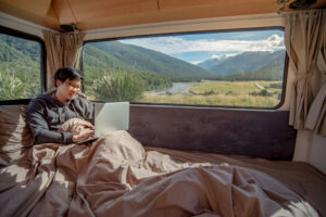 Young Asian man working with laptop in camper van